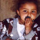 Portrait d'une fillette en tenue traditionnelle, les mains tatouées au henné - Shibam, Yémen, 2000